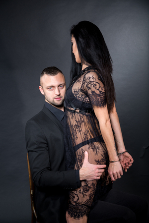 Lovers role-playing games. Dominate obey undress seduce a partner. Handcuffs shackled back. Feel emotions hand touch. Beauty model brunette long hair. Sensual date conceptual idea. Thematic bdsm party