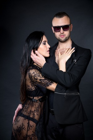 Lovers role-playing games. Dominate obey undress seduce a partner. Feel emotions hand touch. Beauty model brunette long hair. Male sun glass eyeglass. Sensual date conceptual idea. Thematic bdsm party
