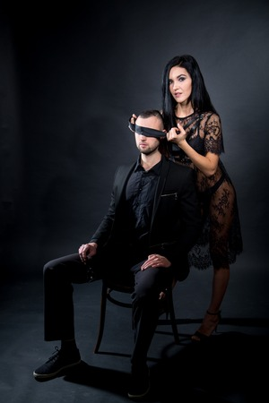 Lovers role-playing games. Dominate obey undress seduce a partner. Boss seating on chair. Feel emotions hand touch. Beauty model brunette long hair. Sensual date conceptual idea. Thematic bdsm party Imagens