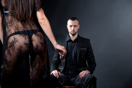 Lovers role-playing games. Dominate obey undress seduce a partner. Feel emotions hand touch. Beauty model brunette long hair. Sensual date conceptual idea. Thematic bdsm party. Background male seating