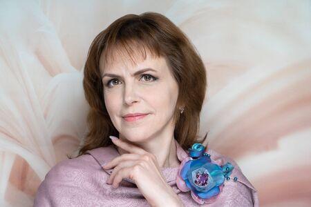 Closeup portrait beautiful woman lady hair styling. Luxury professional makeup aging. Beige shiny lipstick. Sexy smile, blouse shoulders. New photo close up portrait, calm color background horizontal
