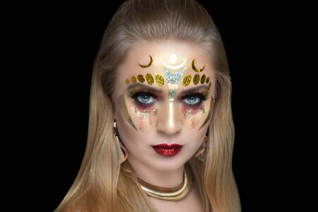 New creative make-up, conceptual idea for Halloween club party. Yellow bold color graphic shapes, cosmetics shadows paints golden lines lips. Professional close-up photo. crazy skin painting artistic