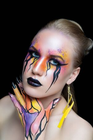 New creative make-up, conceptual idea for Halloween club party. Orange bold color graphic shapes, cosmetics shadows paints black lines lips. Professional close-up photo. crazy skin painting artistic Фото со стока
