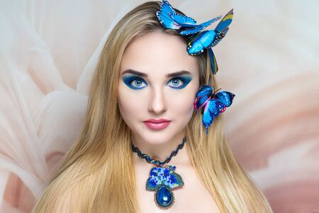 New creative make-up, conceptual idea for Halloween party. Blond hair. Blue color beads necklace, cosmetics shadows paints lines long lashes. Professional close-up photo. natural skincare cream banner Stock fotó
