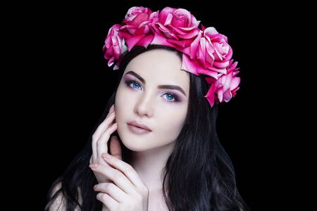 Young beautiful girl, massive accessory flowers crown. Big eyes seductive look. Professional make-up bright shadows pencil technique smoky eyes, good shape eyebrows, matte beige lipstick, manicure Stock fotó