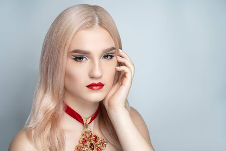 Close up portrait, beautiful adult woman girl, design jewellery, art hairstyle. Face Fashion model, stylish trendy make up, glossy red lipstick. Pretty girl posing at studio, touch fingers her cheek Stock fotó