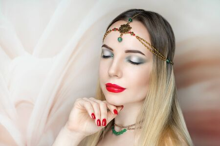 Young beautiful girl, massive gold accessory necklace, tiara. Big eyes dreamy closed. Shamahan make-up bright shiny glitters shadows pencil technique smoky eyes, good shape eyebrows matte red lipstick