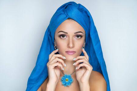 Close up portrait, beautiful adult woman, design accessory flower necklace. Face Fashion model, stylish trendy make up arrows, skincare, beige lipstick. Pretty girl posing at studio. Muslim headdress