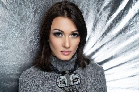 Close up portrait, beautiful adult woman, design beads accessory handmade. Face Fashion model, stylish trendy make up arrows, skincare, beige lipstick. Pretty girl posing at studio. Silver background
