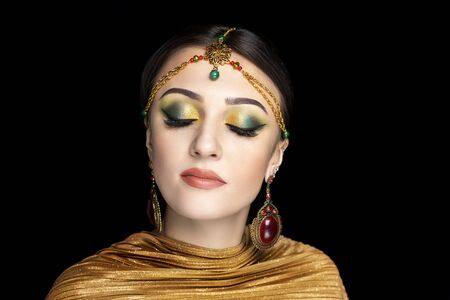 Young beautiful girl, massive gold accessory. Shamahan Beauty dancer. Queen of Samakhan. Big eyes dreamy closed. Professional make-up bright shiny glitters shadows pencil technique green smoky eyes