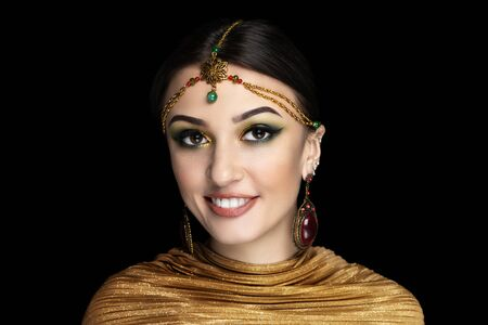 Young beautiful girl, massive gold accessory. Shamahan Beauty dancer. Queen of Samakhan. Big eyes dreamy looking. Professional make-up bright shiny glitters shadows pencil technique green smoky eyes