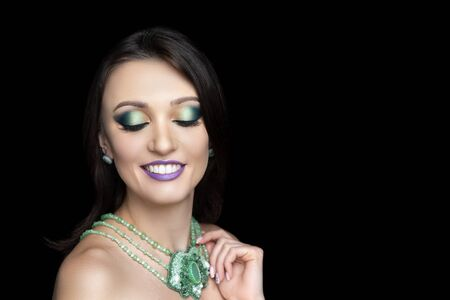 Beautiful girl, massive green accessory. Beauty dancer. Big eyes dreamy closed. Professional make-up bright shiny glitters shadows pencil technique smoky eyes, color gradient. Hand touching necklace