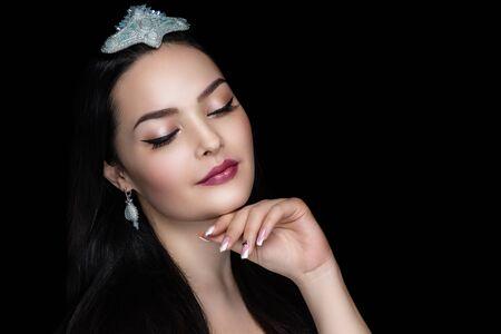 Close up portrait beautiful adult woman, design art jewellery, hairstyle. Face Fashion model stylish trendy make up, glossy lipstick lipgloss. Pretty girl posing at studio, hand touch chin tenderness