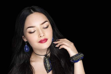 Beautiful woman close up portrait. Professional make up glossy eyeshadows, long lashes, new red matte lipstick. Elegant hair style, massive blue art accessory. Horizontal banner, free place background