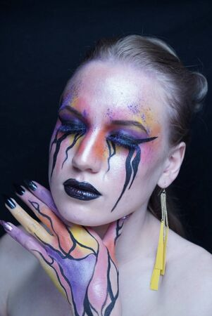 Perfect face young beautiful girl touching her face, bright make-up, purple orange yellow lines of paints flowing from face to hand, mascara tears flow from eyes. Long earrings, manicure black nails Stock fotó - 126865512