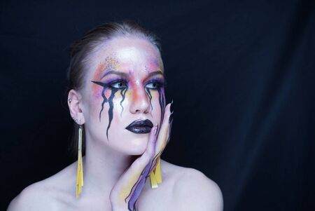 Perfect face young beautiful girl touching her face, bright make-up, purple orange yellow lines of paints flowing from face to hand, mascara tears flow from eyes. Horizontal banner, conceptual idea Stock fotó