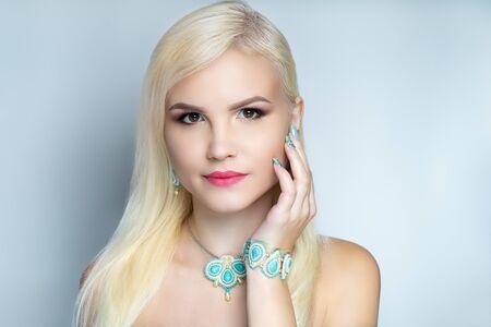 Beautiful woman close up portrait. Professional make up glossy eyeshadows, long lashes, new matte lipstick. Elegant hair style, massive art accessory jewelry. Horizontal banner, light gray background Stock fotó - 127334365