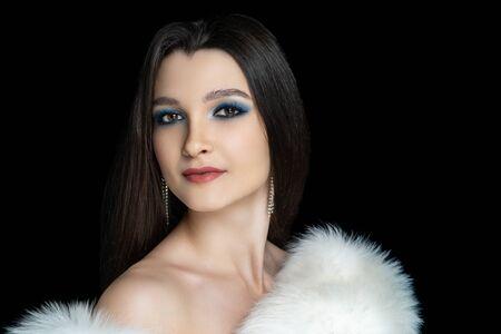 Beautiful woman close portrait. Professional make up glossy eyeshadows, long lashes, new matte lipstick. Elegant hair style, brunette. Horizontal banner black background. Expressive look over shoulder Stock fotó
