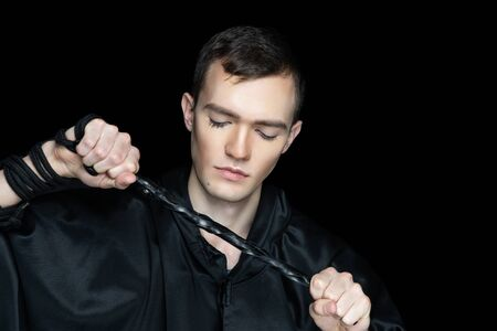 Close up portrait beautiful man, boy, male person, hair cut. Face Fashion model stylish make up, closed eyes, haircare. Pretty persone posing holding black whip, bdsm role play domination submission