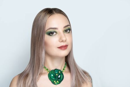 Close up portrait beautiful woman, art jewellery necklace. Face Fashion model stylish trendy green make up, fake lash extensions, opened eyes, glossy lipstick, colored haircare. Pretty girl posing