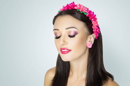 Young beautiful girl, massive accessory flowers crown. Big eyes dreamy closed. Professional make-up bright shiny glitters shadows pencil technique smoky eyes, good eyebrows, matte lipstick, smile lips 写真素材
