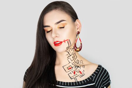 New creative make-up, conceptual idea for Halloween club party. Bold color graphic shapes, cosmetics shadows paints black red lines lips. Professional close-up photo. crazy skin painting artistic