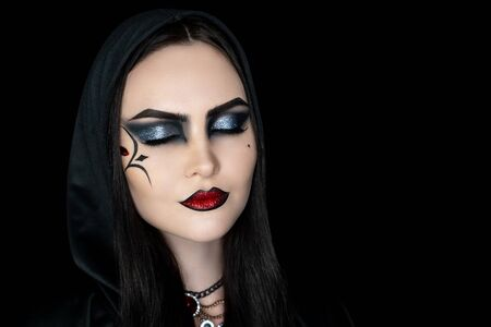 Creative makeup for crazy Halloween party, black lines paint streaks. Big eyes makeup glitters, face evening, glossy glamour lipstick. Original idea for holiday. Professional concept. Young sexy girl