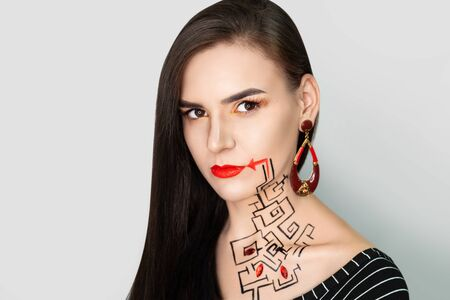 New creative make-up, conceptual idea for Halloween club party. Bold color graphic shapes, cosmetics shadows paints black red lines lips. Professional close-up photo. crazy skin painting artistic Stock fotó - 130497256