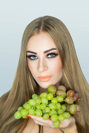 beautiful woman holding near face big green grapes, fresh grape bunch decorates summer garden. beauty make up. Round shape of berries, daylight illuminates. Horizontal banner textured new background