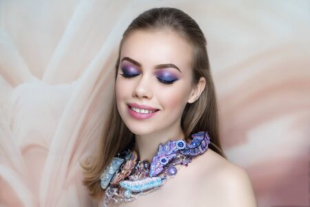 Close-up portrait of beautiful girl pretty lady with professional pink violet blue makeup, arrows long lashes, straight hair styling. Luxury New Bright color make-up shiny lipstick glossy cosmetics
