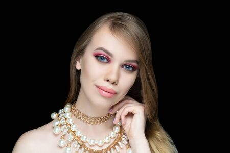Beautiful woman. Bright makeup, shades shadows blending feathering. Evening hairstyle gathered long straight hair. background horizontal night black banner. Big necklace massive chain