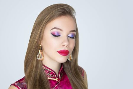 Close-up portrait of beautiful girl pretty lady with professional pink makeup, arrows long lashes, straight hair styling. Luxury New crimson make-up lipstick glossy cosmetics, geisha dress japan