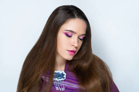 Beautiful woman skincare concept. Bright makeup pink shades crimson shadows. Evening hairstyle long straight hair. background horizontal gray banner. Big massive brooch in a shape of funny rainy cloud 스톡 콘텐츠