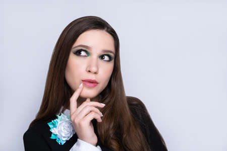 Young beautiful girl looks side and touches her lips thoughtfully. Beauty woman skincare concept. Bright makeup green shades shadows sequins. Evening hairstyle long straight hair brunette. Gray back