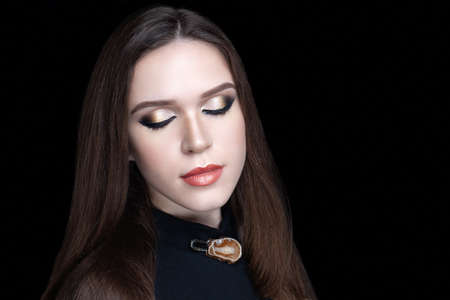 Beautiful woman skincare concept. Bright makeup white gold bronze shades shadows. Evening hairstyle long straight hair. background horizontal black banner. Big massive brooch made of natural gem stone 스톡 콘텐츠