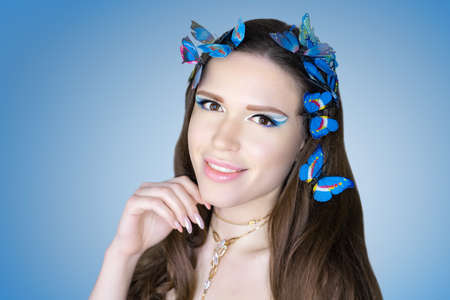 Beautiful woman skincare concept. Bright makeup cut crease in white shades shadows sequins. Evening hairstyle long straight hair, butterfly decorate. background blue banner. Big necklace massive chain
