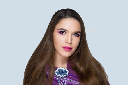 Beautiful woman skincare concept. Bright makeup pink shades crimson shadows. Evening hairstyle long straight hair. background horizontal gray banner. Big massive brooch in a shape of funny rainy cloud 스톡 콘텐츠 - 151912443