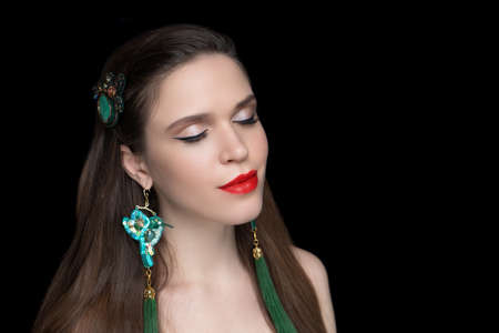 Beautiful woman close up portrait. Professional make up beige eyeshadows, long lashes, new red lipstick. Elegant hair style, massive green accessory long ear rings. Horizontal banner, black background