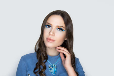 Young beautiful girl puts on blue denim blouse. Massive necklace colorful crystals. Traditional ornaments embroidery. Professional make-up pencil technique cut crease, lips. Long curly hair, brunette 스톡 콘텐츠