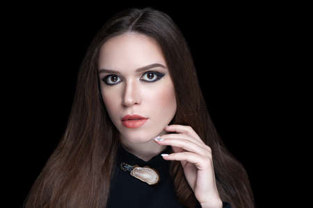 Young beautiful girl looks emotionally and touches her chin thoughtfully. Sexy beauty woman, skincare concept. Bright makeup smoky eyes shadows sequins. Evening hairstyle long straight hair brunette