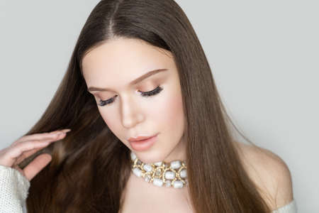 Beautiful woman skincare concept. Bright makeup golden shades shadows sequins, nude lipstick. Evening hairstyle long straight hair. background horizontal gray banner. Big necklace massive chain beads 스톡 콘텐츠