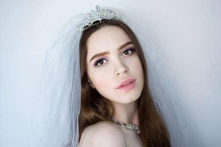 Beautiful woman bride close up portrait. Professional make up glossy eyeshadows, long lashes, new lipstick on big lips. Elegant hair style, sheer veil mesh. Horizontal banner, free place background 스톡 콘텐츠