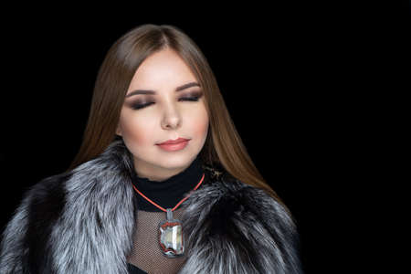 Beautiful girl puts on a gorgeous fur coat made of expensive silver fox fur. Luxury jewelery decorates her neck, exclusive necklace made of gem stones. Perfect horizontal banner for new clothes store 스톡 콘텐츠