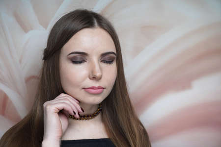 Young beautiful woman with brown makeup smoky eyes. Long straight hair, gathered hair-do. Professional make up, nude matte lips - waterproof lipstick. Dreamy closed eyes, touching her chin by fingers