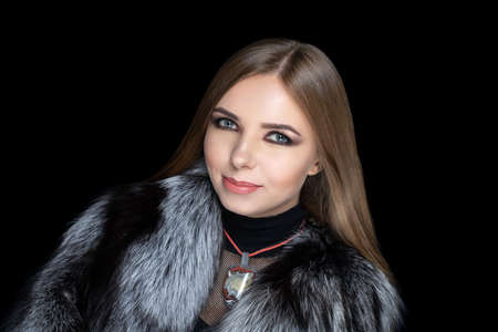 Beautiful girl puts on a gorgeous fur coat made of expensive silver fox fur. Luxury jewelery decorates her neck, exclusive necklace made of gem stones. Perfect horizontal banner for new clothes store