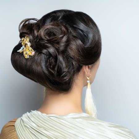 Close-up portrait of beautiful girl with volume hair-do. Luxury hair styling. Woman with gathered medium length hair. Wedding hairstyle decorated by accessory. Beauty bride style, creative jewelry pin Imagens - 152000288