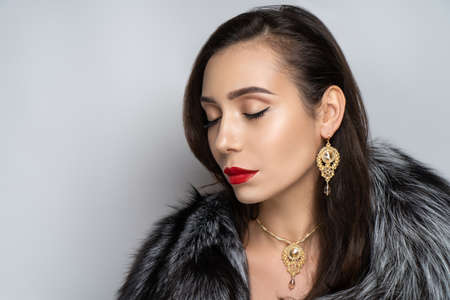 Beautiful girl puts on a gorgeous fur coat made of expensive silver fox fur. Luxury jewelery decorates her neck, exclusive necklace made of gem stones. Perfect horizontal banner for new clothes store 스톡 콘텐츠 - 152000296