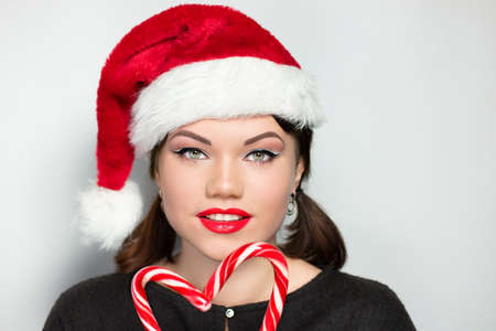 Young beautiful girl with black short hair holding candy lollipop in her hands. Professional portrait photo for a New year party. Manicure, makeup red lips, new lipstick with a glossy effect. Xmas hat 스톡 콘텐츠