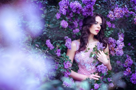 beautiful girl with dark hair in a pink dress standing in the garden lilac bushes