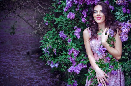 light hair: beautiful girl with dark hair in a pink dress standing in the garden lilac bushes